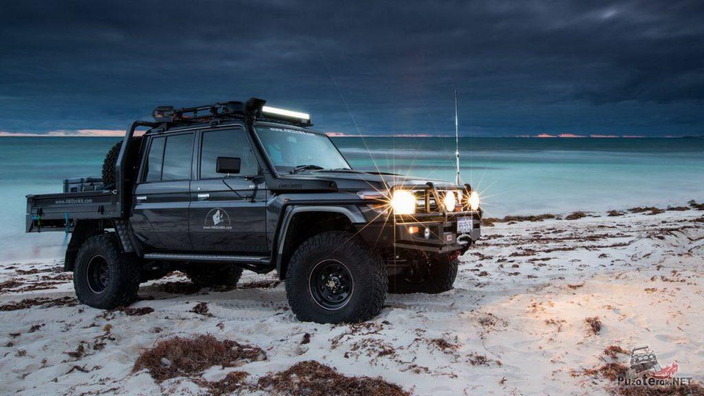 Лифтованный пикап Toyota Land cruiser на больших колесах на берегу озера.