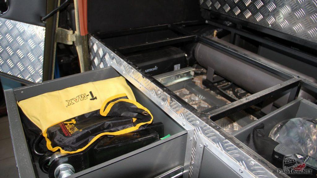 Местонахождение компрессора и ресивера не сразу поддается определению: они спрятаны между ящиками багажника и задним диваном.