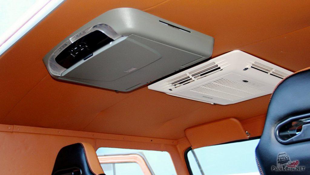 На потолке находится кондиционер и мультимедиа система с телевизором