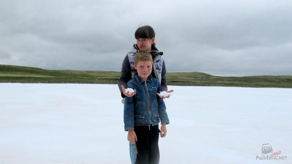 Дети лепят снежки в июле