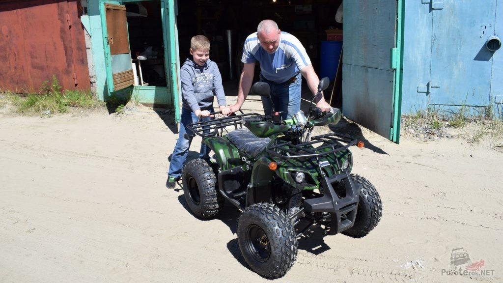 Папа с сыном выводят из гаража новый квадроцикл