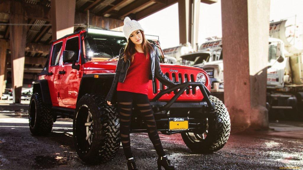 Девушка в красном рядом с красным джипом