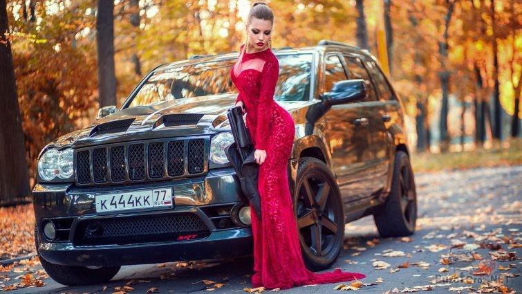 Девушка в красном вечернем платье вынимает карабин
