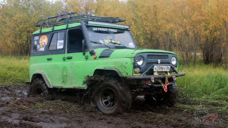 Зеленый УАЗ Хантер едет по торфянику