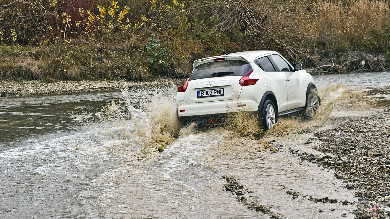 Белый паркетник Ниссан пробирается по руслу речки в осеннем лесу