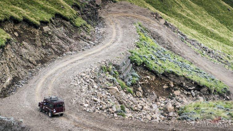 Бордовый внедорожник на серпантине перевала Сани Пасс