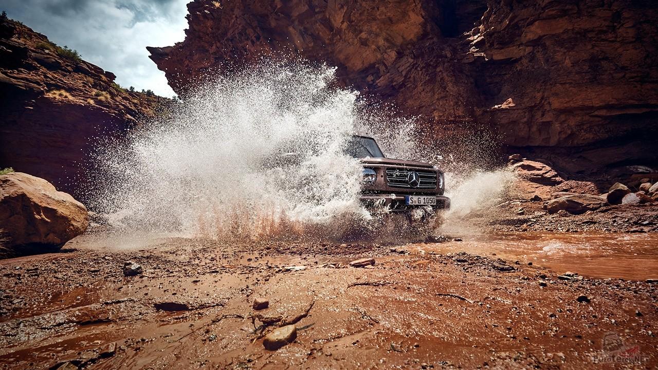 Гелендваген поднимает фонтан брызг выезжая из горной речки на скалистый берег