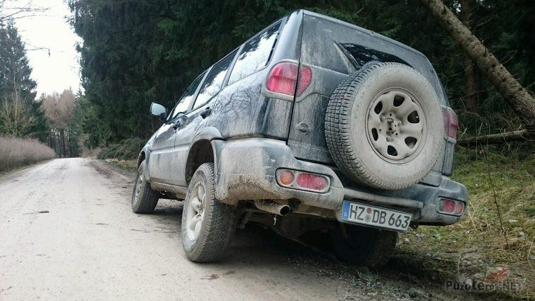 Грязный, пыльный внедорожник Ниссан Тиррано 2 на обочине лесной дороги