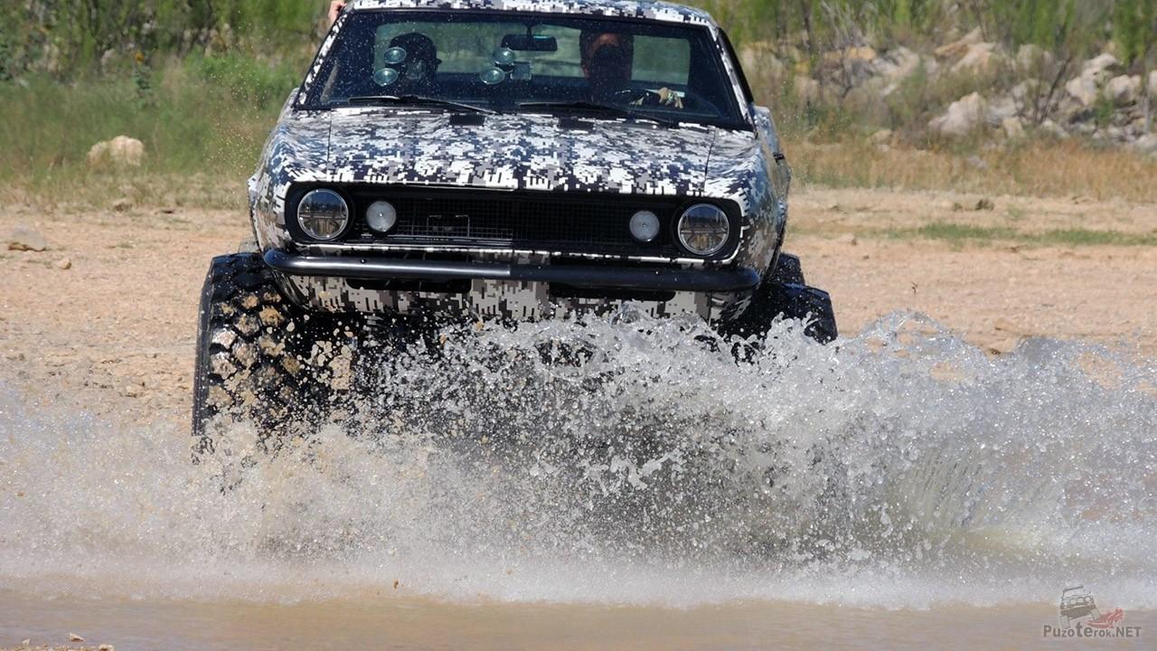 Камуфлированный Шевроле Камаро бигфут мчится по бездорожью переская реку