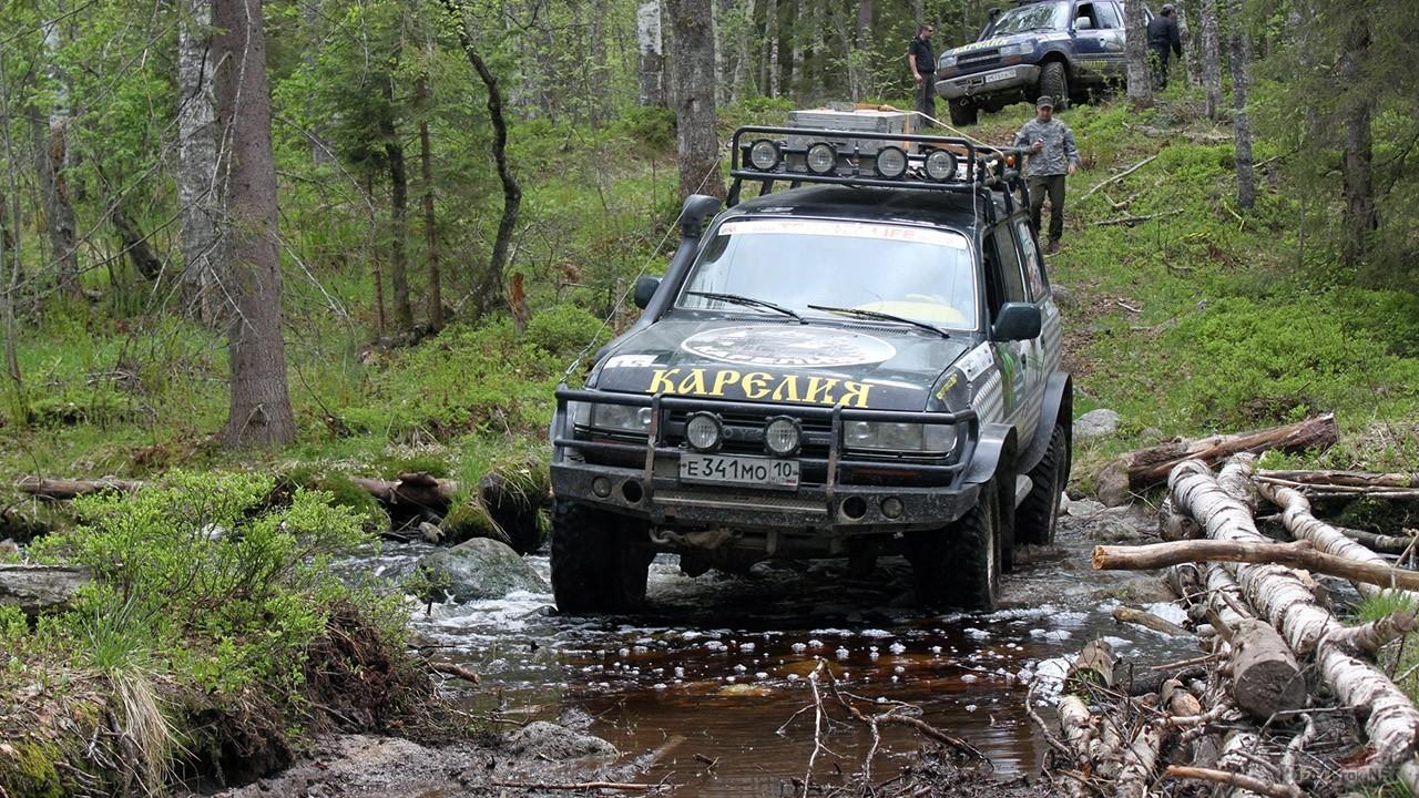 Караван джипов пересекает лесную речку в Карелии