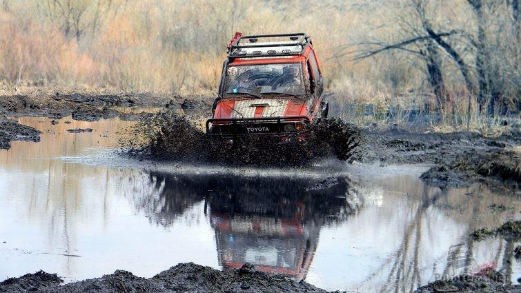 Красный джип Тойота пробирается вброд по болотистой местности