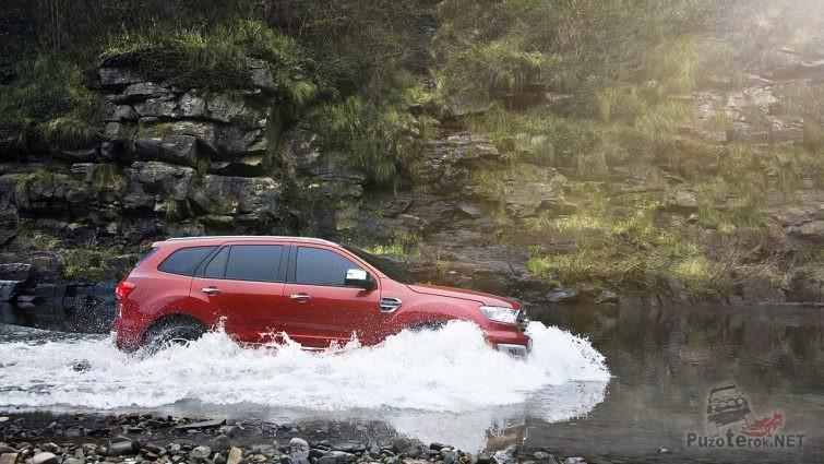 Красный внедорожник рассекает воды горной реки