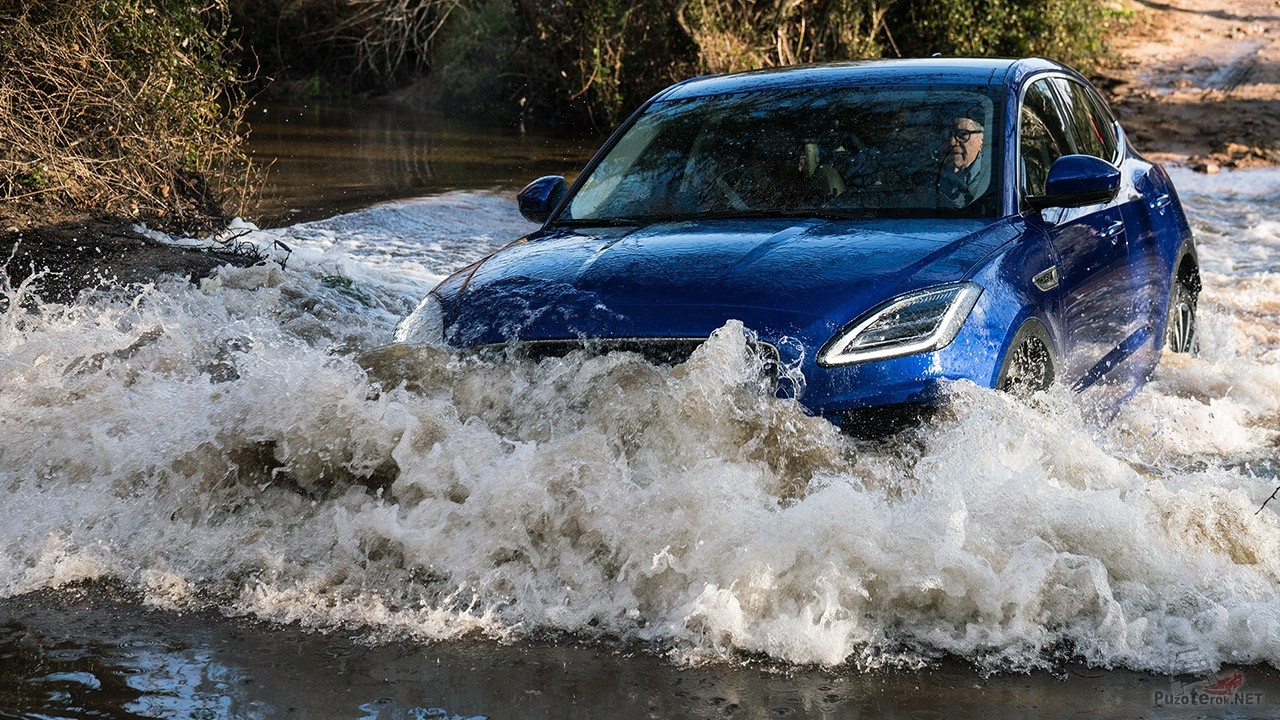 Мужчина за рулём тёмно-синего внедорожника Ягуар на речной переправе