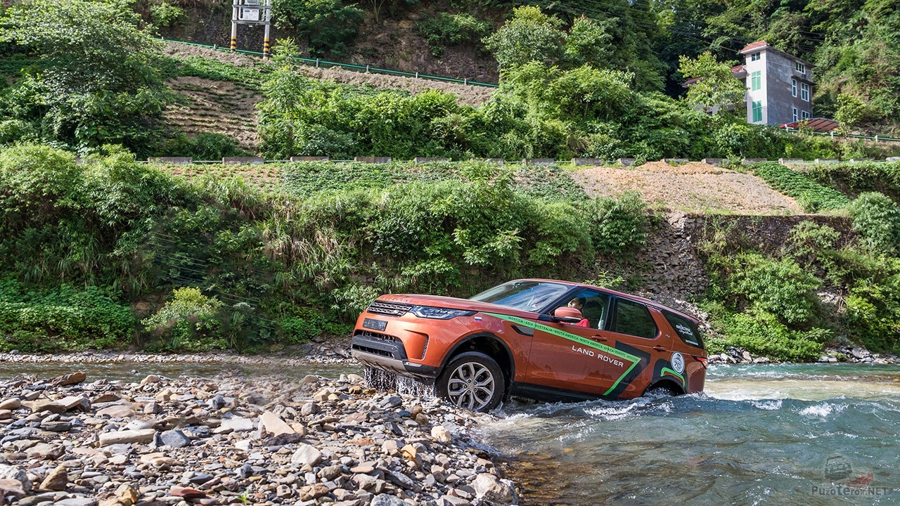 Оранжевый внедорожник Лендровер выбирается из брода на каменистый берег