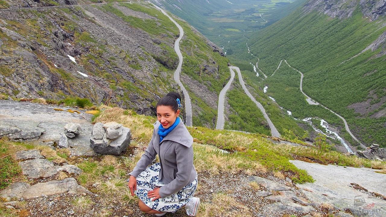 Туристка позирует на фоне серпантина горного перевала Дорога Троллей в Норвегии