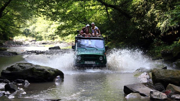 Туристы на джиппинге в Абхазии едут по руслу горной речки