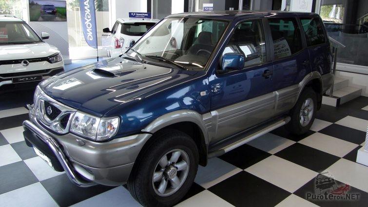 Тёмно-синий Ниссан Террано второго поколения на стенде автосалона продаж