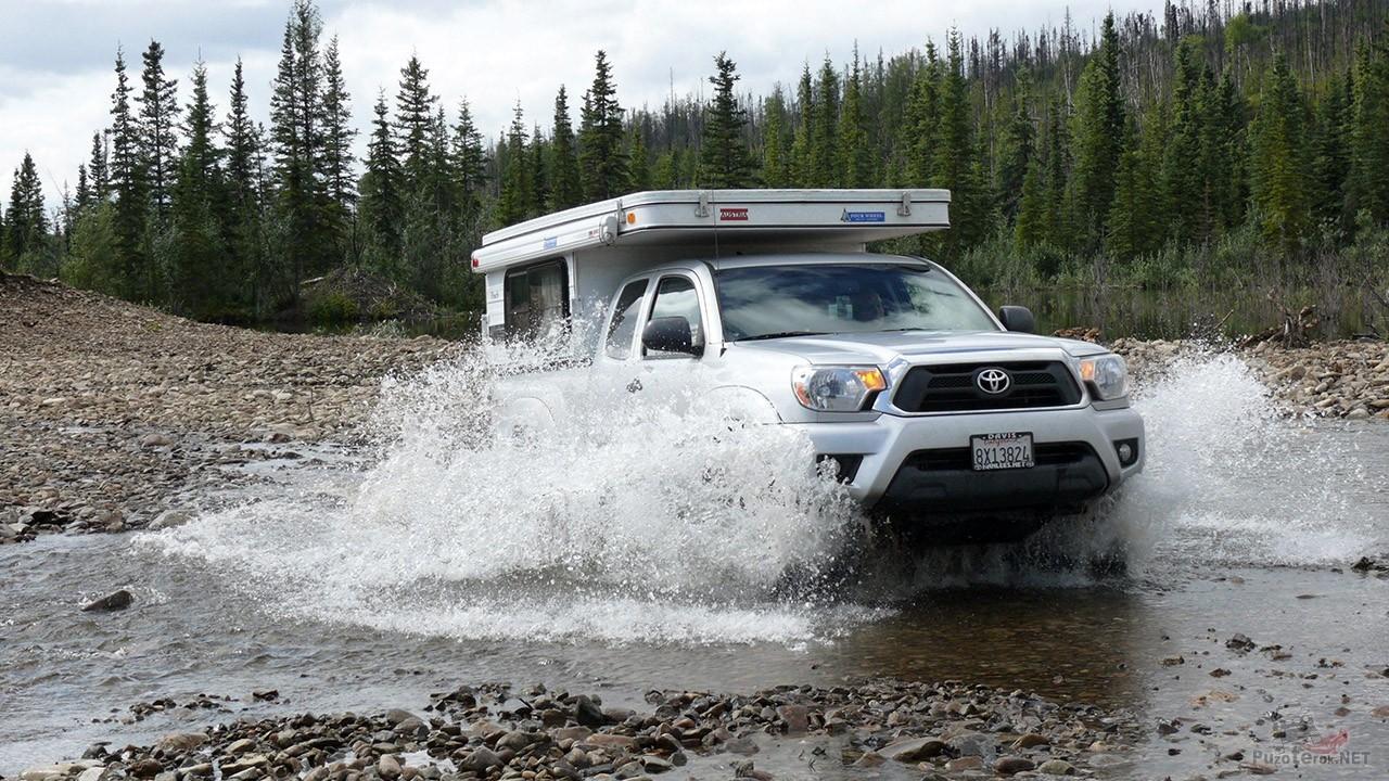 Внедорожник с фургоном мчится через мелкую горную речку