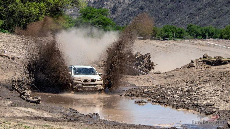 Внедорожник вздымает тайфун брызг грязи проезжая по руслу пересохшей горной речки