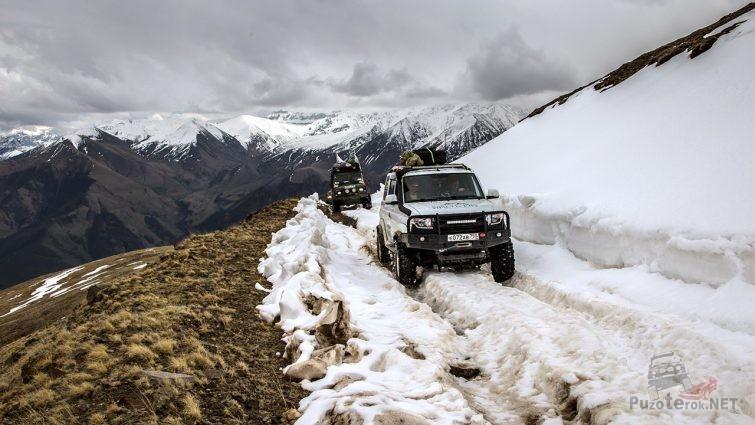 Внедорожники на заснеженной горной дороге Центрального Кавказа