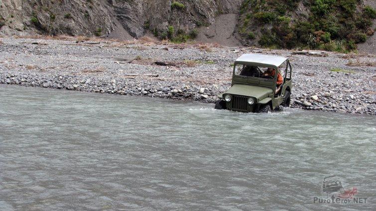 Военный Виллис начинает переправу вброд через полноводную горную реку