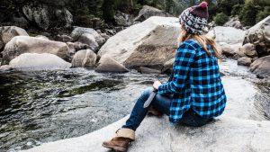 Девушка на берегу горной реки с ножом в руках