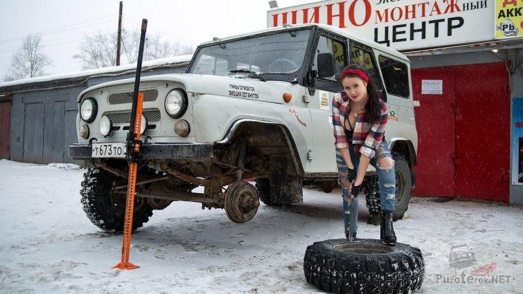 Девушка ремонтирует колесо УАЗика