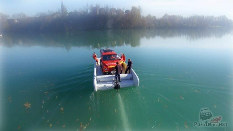 Красный джип на надувной лодке для автопереправы