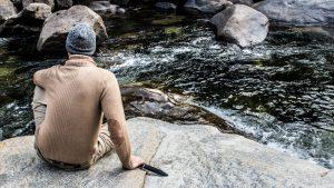 Мужчина с ножом Survivalist на берегу горной реки