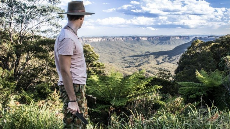 Мужчина с ножом для выживания на фоне австралийского каньона
