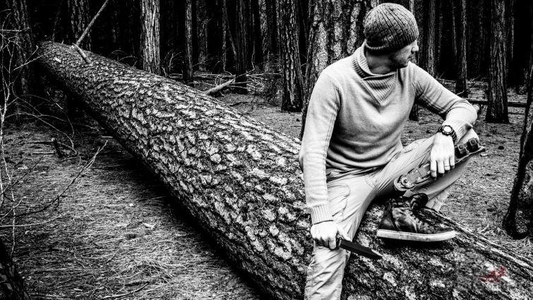 Мужчина в лесу с ножом выживальщика