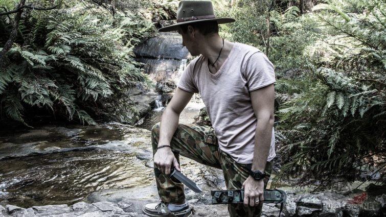 Мужчина в лесу у ручья с ножом выживальщика
