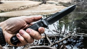 Нож Trident на фоне реки в мужской руке
