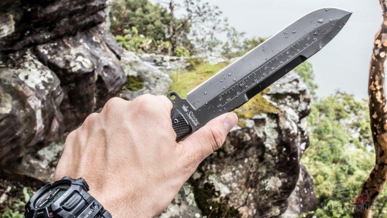 Нож для выживания в руке на фоне скальника
