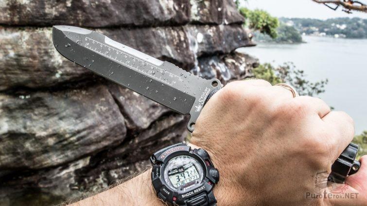 Нож в руке с наручными часами