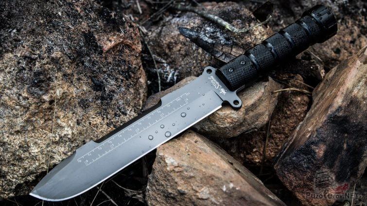 Нож выживальщика на камнях костровища