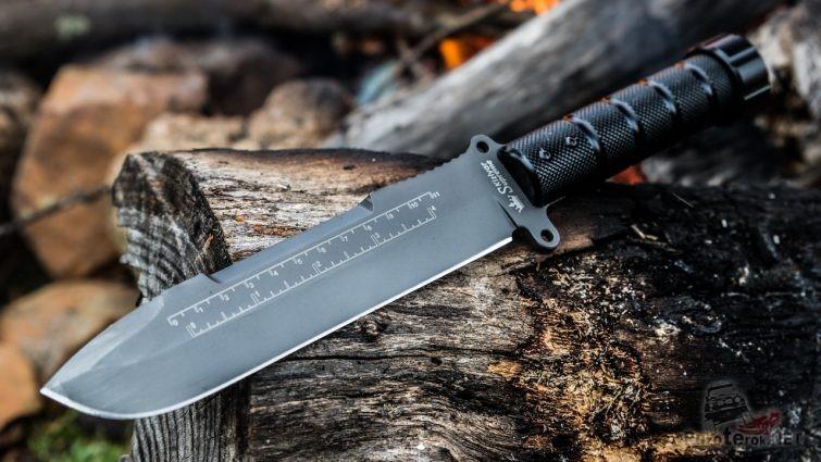 Нож выживальщика на обугленном бревне костра