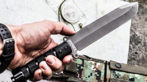 Нож выживальщика в мужской руке на фоне карты