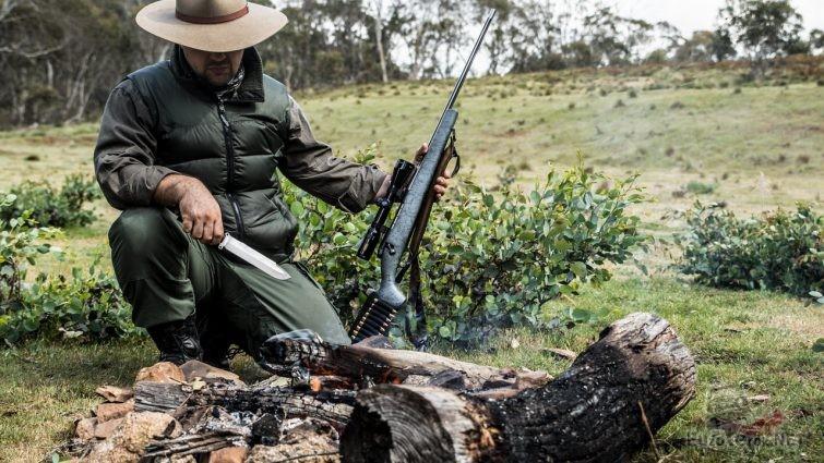 Охотник с ножом и винтовкой у костра