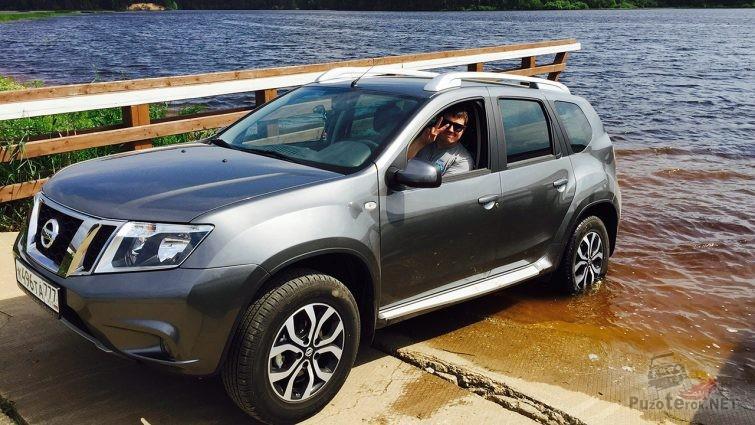 Счастливый водитель за рулём внедорожника Ниссан Террано 3 на мелководье лесной реки