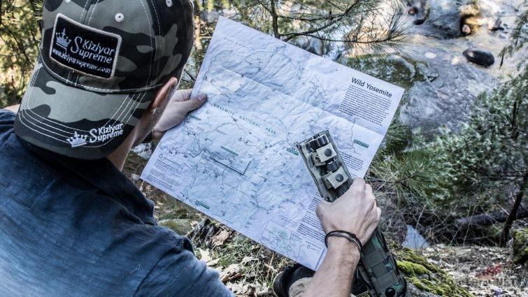 Турист в фирменной кепке с ножом для выживания и картой местности