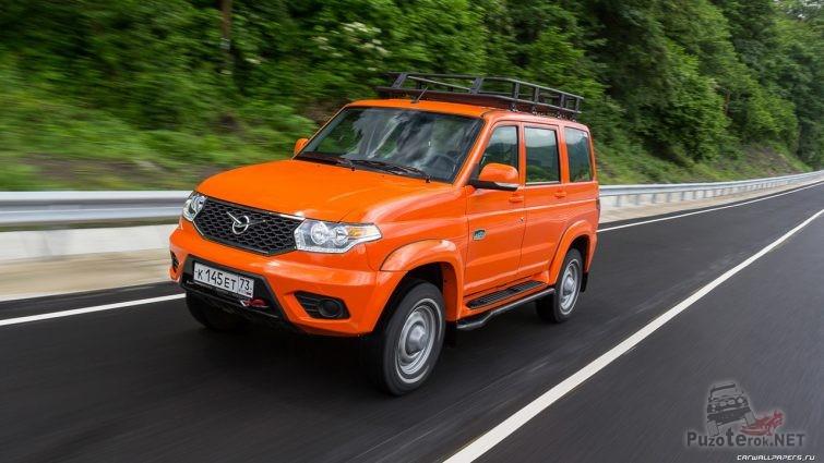 Оранжевый экспедиционный Патриот едет по дороге
