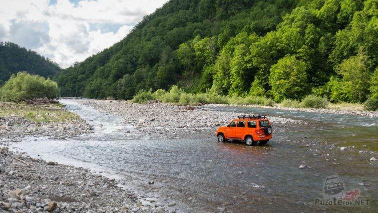 Экспедиционный патриот на мелководье горной реки