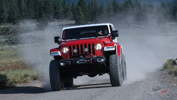 Jeep Jeepster на больших колёсах мчится по гравийной дороге