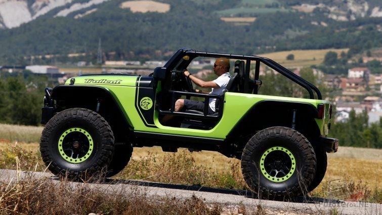 Jeep Trailcat по дороге на фоне гор