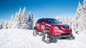 Красный икс-трейл на гусеницах на снежном склоне