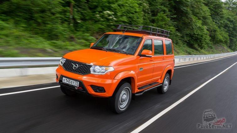Оранжевый УАЗ Патриот мчится по шоссе