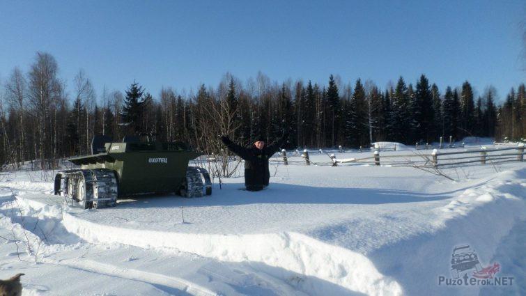 Человек в глубоком снегу с рядом стоящим вездеходом Охотец