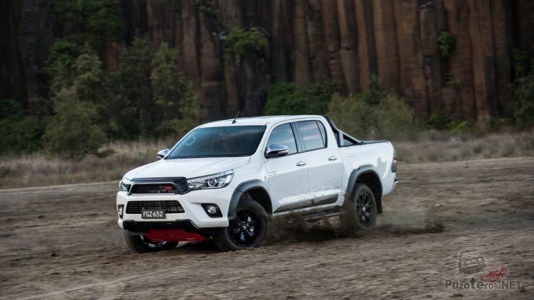 Белая Тойота Хайлюкс дрифтует на фоне скал