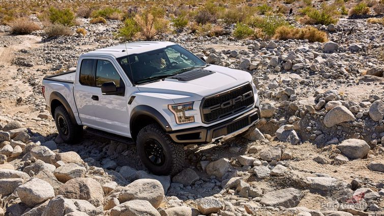Белый Ford Раптор едет по камням